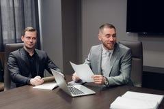 Hombres de negocios jovenes que discuten el trabajo durante una presentación del negocio en la sala de conferencias imágenes de archivo libres de regalías