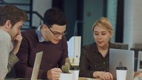 Hombres de negocios jovenes que discuten en sala de reunión en la oficina creativa metrajes