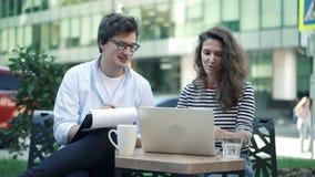 Hombres de negocios jovenes que discuten su proyecto en café del aire libre metrajes