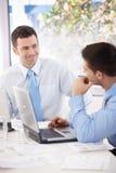 Hombres de negocios jovenes que hablan en la mesa de reuniones Fotografía de archivo libre de regalías