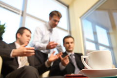 Hombres de negocios jovenes que hablan en una oficina - falta de definición