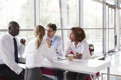 Hombres de negocios jovenes que hablan sobre el café en un pasillo moderno foto de archivo