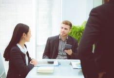 hombres de negocios jovenes que hacen la reunión y que hablan para analizar el márketing Foto de archivo libre de regalías