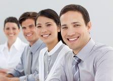 Hombres de negocios jovenes que se sientan en una línea Imágenes de archivo libres de regalías