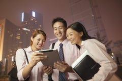 Hombres de negocios jovenes que sonríen y que trabajan al aire libre en la noche Imagen de archivo libre de regalías
