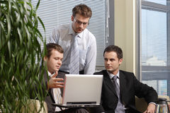 Hombres de negocios jovenes que trabajan con el latop en oficina Fotografía de archivo libre de regalías