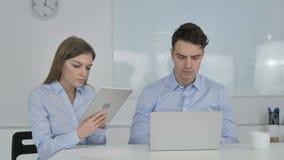 Hombres de negocios jovenes que trabajan en la tableta y el ordenador portátil metrajes