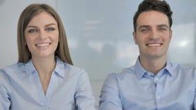 Hombres de negocios jovenes sonrientes que miran la cámara en la oficina, colegas metrajes