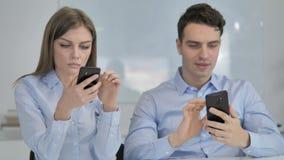 Hombres de negocios jovenes usando Smartphone en el trabajo metrajes
