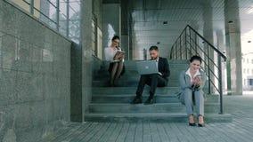 Hombres de negocios jovenes y atractivos que trabajan en las escaleras usando el ordenador portátil, la tableta y el smartphone almacen de metraje de vídeo