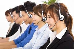 Hombres de negocios jovenes y colegas que trabajan en centro de atención telefónica Fotos de archivo libres de regalías
