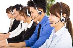 Hombres de negocios jovenes y colegas que trabajan en centro de atención telefónica Foto de archivo