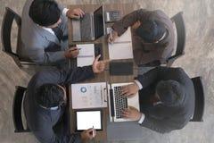 Hombres de negocios jovenes y empresario que tienen una reunión alrededor de t fotografía de archivo