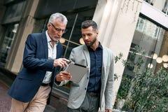 Hombres de negocios jovenes y mayores que usan la tableta digital al aire libre en el fondo de la ciudad fotos de archivo libres de regalías