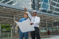 Hombres de negocios jovenes y opinión de los ingenieros los encargados co de la construcción foto de archivo libre de regalías