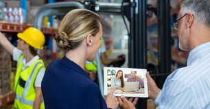 Hombres de negocios de la comunicación video en la tableta en almacén foto de archivo