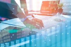 Hombres de negocios de la exposición doble que trabajan en la oficina Mercados de acción financieros o estrategia de inversión imagenes de archivo
