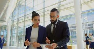 Hombres de negocios de la raza mixta que discuten sobre la tableta digital en el pasillo en la oficina 4k metrajes