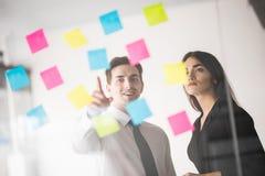 Hombres de negocios de lanzamiento dos del trabajo diario de trabajo en la oficina moderna con las etiquetas engomadas hombre señ Imagen de archivo libre de regalías