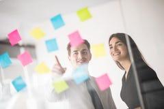 Hombres de negocios de lanzamiento dos del trabajo diario de trabajo en la oficina moderna con las etiquetas engomadas Oficina de Foto de archivo libre de regalías