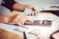 Hombres de negocios de las manos en una calculadora para calcular economía de la renta con los dólares de EE. UU. en la tabla al  fotos de archivo
