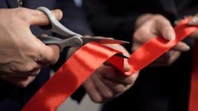 Hombres de negocios de las manos que cortan el primer rojo de la cinta, nuevo proyecto, ceremonia de inauguración imagenes de archivo
