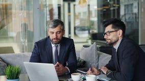 Hombres de negocios maduros que hablan en el café que mira la pantalla del ordenador portátil que discute el contrato metrajes