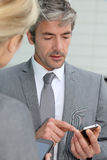 Hombres de negocios maduros que intercambian números de teléfono Imagen de archivo libre de regalías