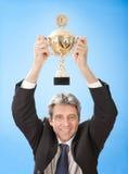 Hombres de negocios mayores que sostienen un trofeo foto de archivo libre de regalías