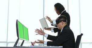 Hombres de negocios de mediana edad que sientan y que ven el contenido del dispositivo de la realidad virtual almacen de video