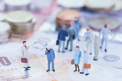 Hombres de negocios miniatura en los billetes de banco de libra esterlina fotos de archivo libres de regalías