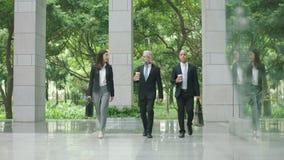 Hombres de negocios multiétnicos del edificio moderno que entra que habla que camina