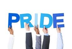 Hombres de negocios multiétnicos que llevan a cabo orgullo de la palabra Imagen de archivo libre de regalías