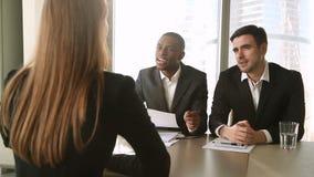 Hombres de negocios multiculturales que conducen la entrevista de trabajo, haciendo preguntas al candidato femenino almacen de video