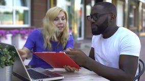 Hombres de negocios nerviosos que discuten, mirando el ordenador portátil y el cartón, problemas almacen de metraje de vídeo