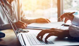 Hombres de negocios o doctor que hablan con el cliente y que usan el ordenador portátil a imágenes de archivo libres de regalías