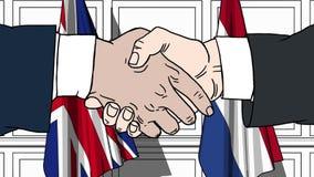 Hombres de negocios o políticos que sacuden las manos contra banderas de Gran Bretaña y de Países Bajos Reunión o cooperación rel almacen de video
