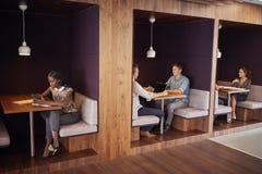 Hombres de negocios ocasional vestidos y empresarias que se encuentran y que trabajan en cubículos en oficina moderna fotografía de archivo libre de regalías