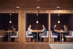 Hombres de negocios ocasional vestidos y empresarias que se encuentran y que trabajan en cubículos en oficina moderna foto de archivo