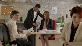 Hombres de negocios de pertenencia étnica mezclada que trabajan en la oficina, hombre negro que viene a la mujer y que habla, hom almacen de metraje de vídeo