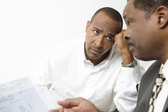 Hombres de negocios preocupantes sobre costos financieros Imágenes de archivo libres de regalías