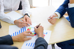 Hombres de negocios que analizan resultados financieros en gráficos alrededor de la tabla en oficina moderna Concepto del trabajo fotos de archivo