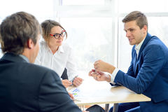 Hombres de negocios que analizan resultados financieros en gráficos alrededor de la tabla en oficina moderna Concepto del trabajo Imagen de archivo libre de regalías