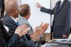 Hombres de negocios que aplauden durante la presentación Fotografía de archivo libre de regalías