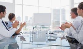 Hombres de negocios que aplauden en un whiteboard en blanco Imagen de archivo