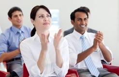Hombres de negocios que aplauden en una conferencia Imagenes de archivo