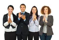 Hombres de negocios que aplauden en una fila foto de archivo