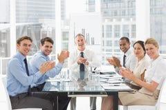 Hombres de negocios que aplauden la cámara en una reunión fotografía de archivo libre de regalías