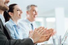 Hombres de negocios que aplauden las manos durante un seminario Fotos de archivo libres de regalías
