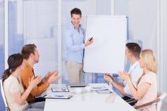 Hombres de negocios que aplauden para el colega después de la presentación Foto de archivo